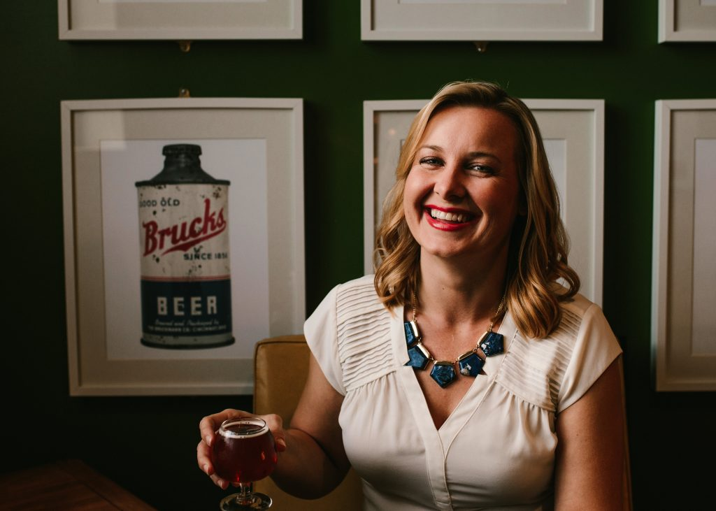 Kristen Thomas - Open the Doors, Owner laughing, holding a tulip shaped beer glass with a dark beer. An antique Brucks beer sign is in the background.